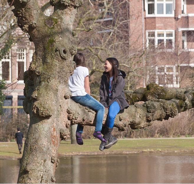 Foto van spelende kinderen aan de rand van het water in de stad