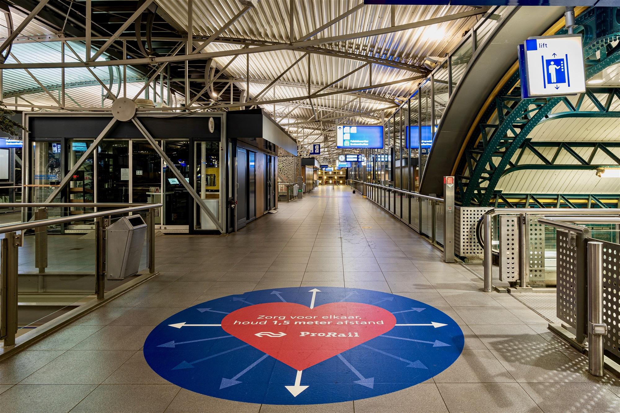foto van stationstraverse met grote sticker op de grond met tekst 'Zorg voor elkaar, houd 1,5 m afstand'