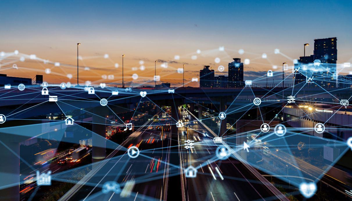 Verlichte snelweg met denkbeeldige draadstructuur van digitale verbindingen en stedelijke bebouwing op achtergrond
