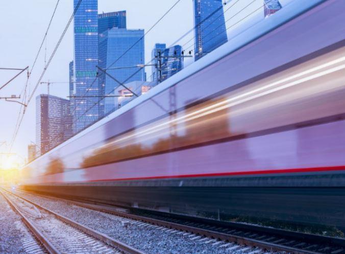 hogesnelheidstrein rijdt door de stad, bewogen beeld van de trein met gebouwen op de achtergrond