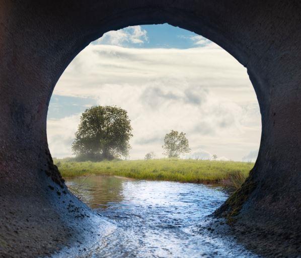 Doorkijk naar natuur vanuit buis met waterafvoer