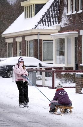 kinderen spelen met een sleetje in de sneeuw in een woonwijk