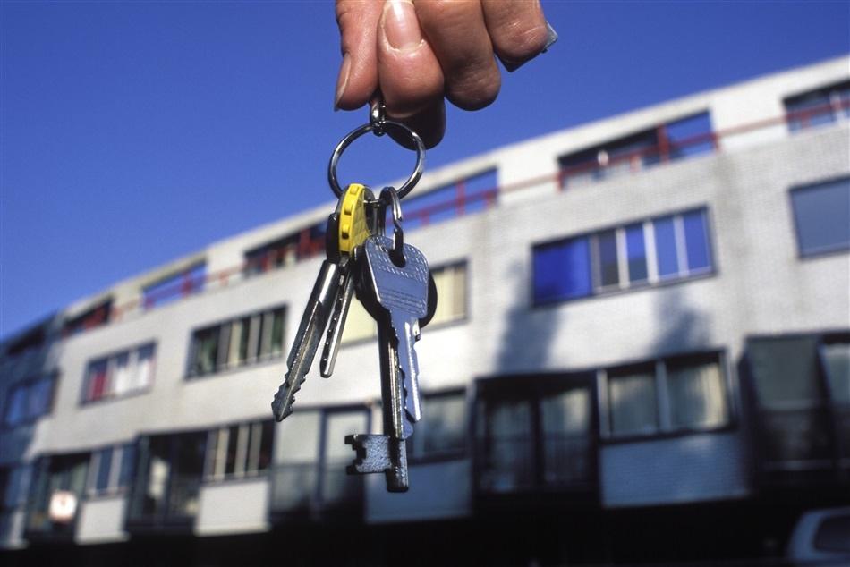 Foto van sleutels met op de achtergrond woningbouw