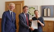 Raadslid Krijn Poppe (l) en voorzitter Rli Jan Jaap de Graeff (m) overhandigen het advies aan minister Schouten LNV Foto: Fred Ernst