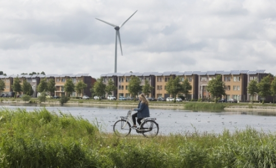 foto: fietser langs een vaart met woningen met zonnepanelen en windmolen op de achtergrond