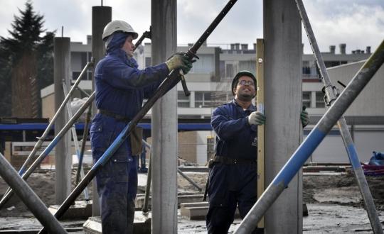 foto van bouwvakkers aan het werk op stijger met in aanbouwzijnde woningen op de achtergrond