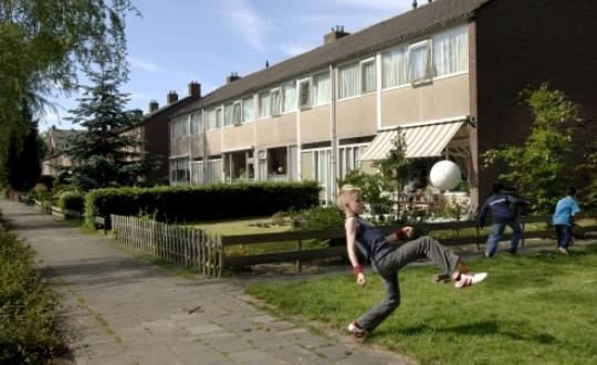 foto van spelend kind met bal op veldje in een woonwijk
