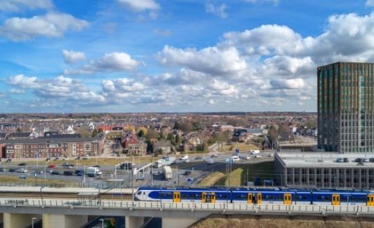 verkeersplein van de Prins Mauritssingel en de Graaf Alardsingel in Nijmegen, met vrachtverkeer en auto's en op de voorgrond een spoorbrug met trein (een zogenaamde sprinter) bij station Nijmegen Lent met op de achtergrond de bebouwing van de Nijmeegse wijk Lent