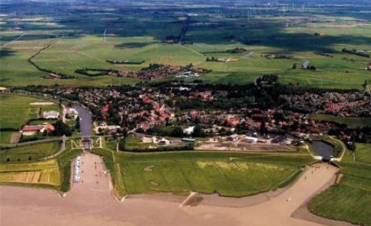 Luchtfoto van dorp aan Eems estarium