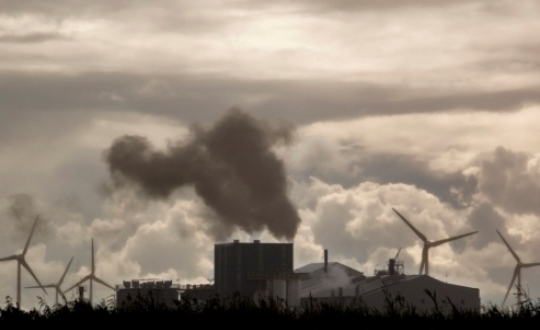 fabrieksschoorstenen met windmolens op de achtergrond