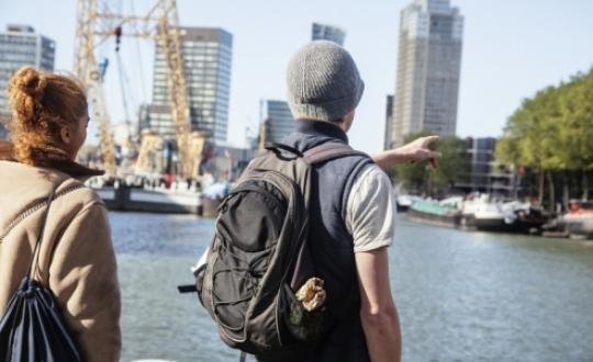 Toeristen wijzen richting haven Rotterdam als symbool voor maiports voorbij
