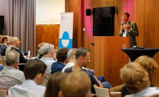 foto van de zaal met deelnemers aan het symposium