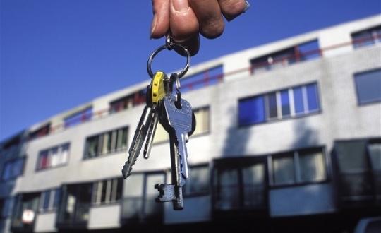 foto van huissleutels met op de achtergrond een woonwijk
