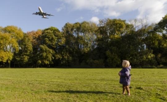 foto met kind in park en vliegtuig hoog overvliegend