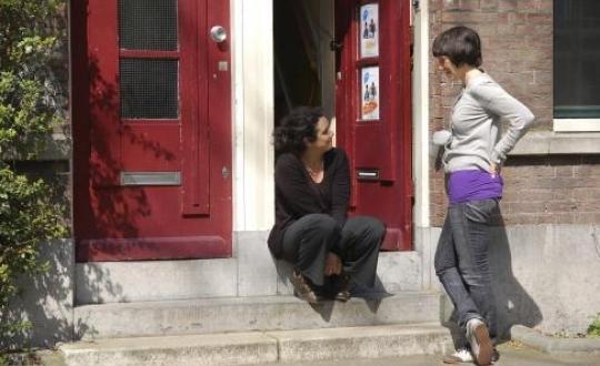 foto twee vrouwen op stoep; open en dichte voordeur