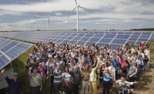 veld met zonnepanelen en windmolens met op de voorgrond een groep enthousiaste mensen